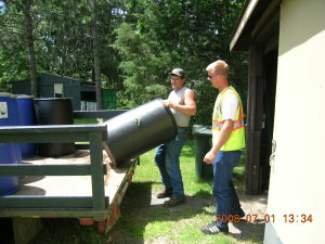 2 men loading up a water barrel onto a truck